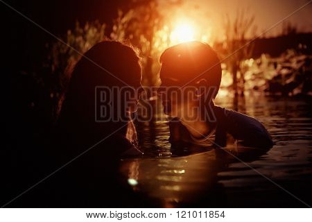 Young Couple Is Kissing In The River