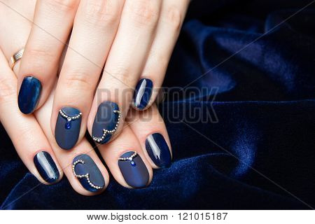 French manicure - beautiful manicured female hands with blue manicure with rhinestones on dark blue