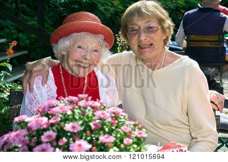 Two affectionate senior women enjoying coffee.
