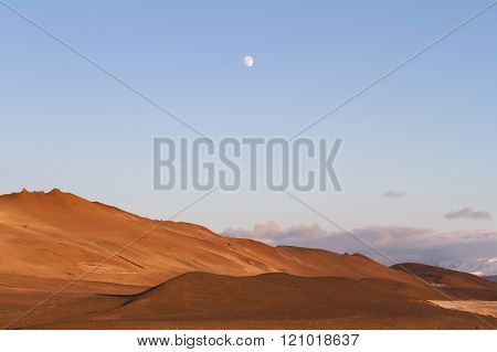 Red Tinted Volcanic Mountains With Moon Rising Above