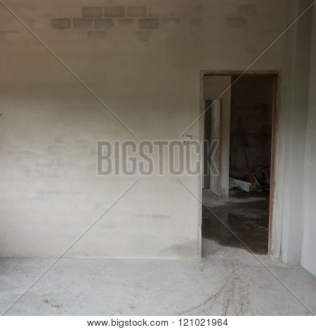 Empty Cement Concrete Room In Construction Site With Door Entrance