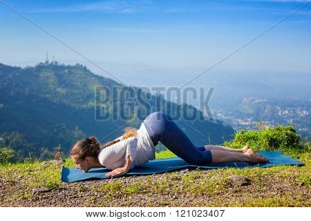 Woman doing yoga asana Ashtangasana eight-limbed pose outdoors in mountains in the morning in Himalayas