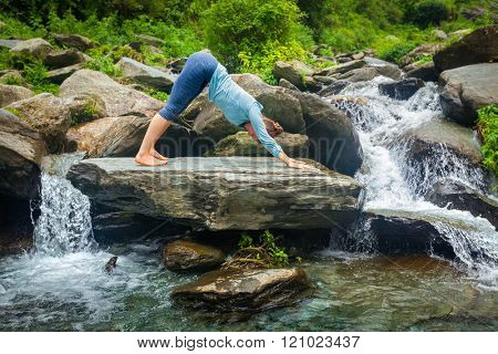 Young sporty fit woman doing yoga asana Adho mukha svanasana - downward facing dog - at tropical waterfall
