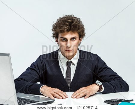 Ambitious young businessman looking at camera with serious look.