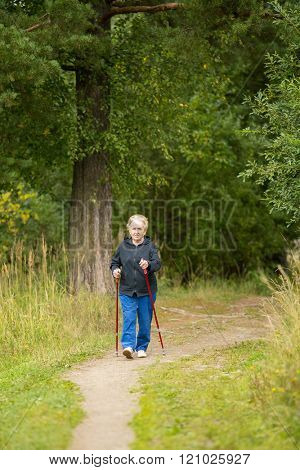 An elderly woman is engaged in Nordic walking in the nature.