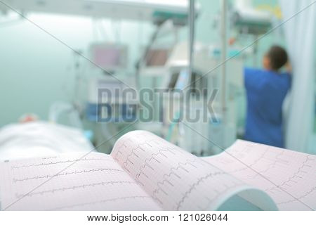 Ecg At The Background Of Medical Staff Working With The Patient In Hospital Ward