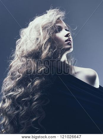 Beautiful brunette woman with beauty long curly hair. Fashion photo