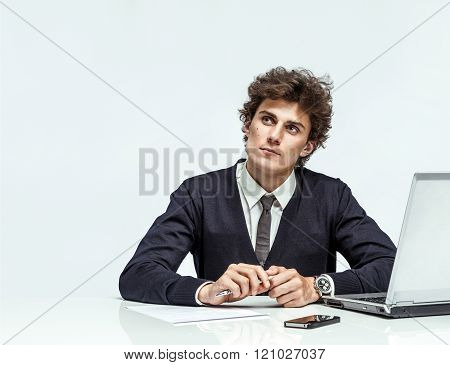 Businessman with doubtful expression looking up into the corner.