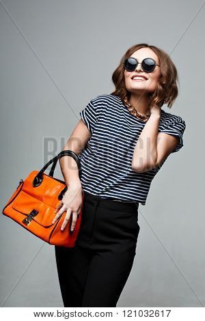 Fashionable woman with an orange bag and Large Round Sunglasses.
