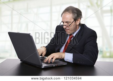 mature business man working with his laptop at the office