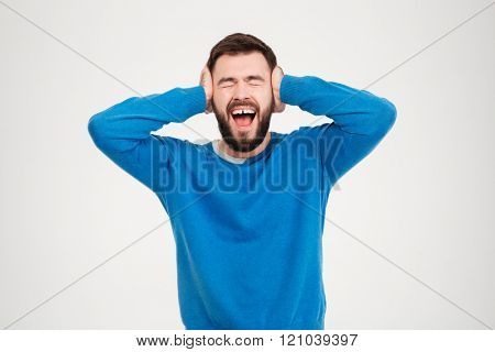 Young man covering his ears and screaming isolated on a white background