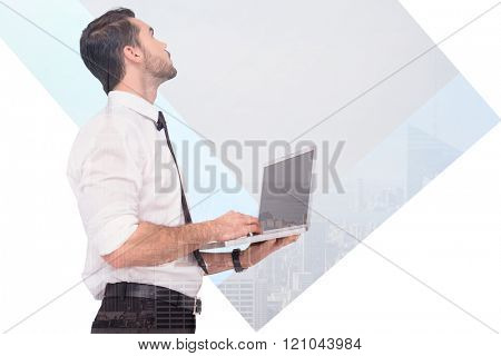 Sophisticated businessman standing using a laptop against cityscape