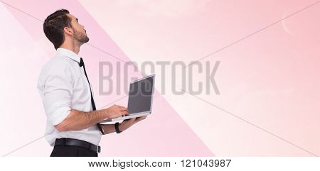 Sophisticated businessman standing using a laptop against green field under blue sky