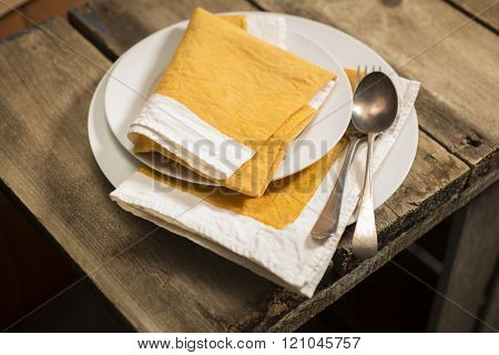 Dinner Plates And Orange Napkins Stack With Spoon And Fork