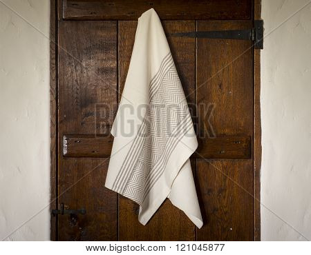 White Towel With Gray Herringbone And Stripes Hanging On  Door