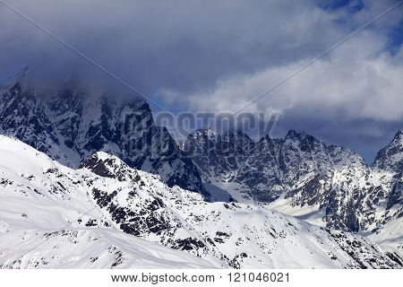 Snowy Rocks In Clouds At Sunny Day