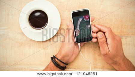 American football player scoring a touchdown against hands holding smartphone next to cup of coffee