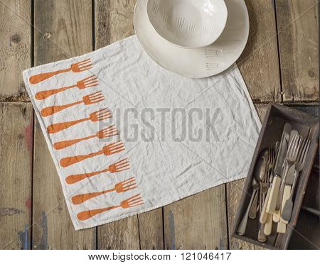 White Napkin With Orange Fork Pattern Alongside Flatware And Tray