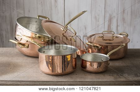 A set of copper cookware that include a small and medium-sized saucepan at front a large saucepan pot and cover stacked on top of the other and a covered small pot bringing up the rear all placed on a wooden countertop.