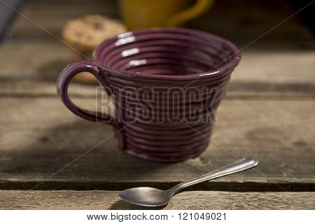 Empty Brown Teacup Beside Spoon With Cookies In The Background
