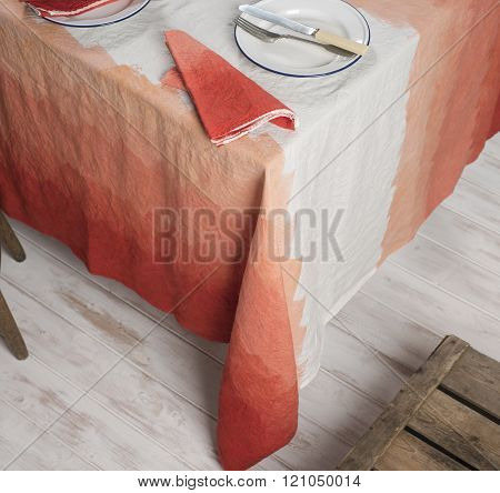 Dinnerware And Napkin On Table Covered In Gradient Orange Zigzag Linen