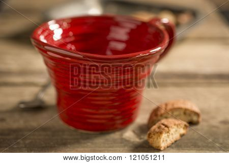 Empty Red Teacup Between Spoon And Biscuits