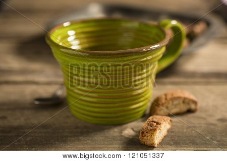 Empty Green Teacup, Framed At Center, Between Spoon And Biscuits