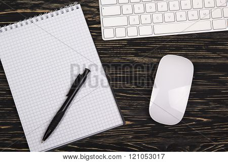 Mix of office supplies and gadgets on a wooden background.