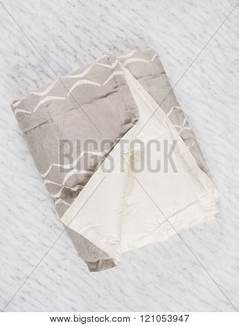 Folded Gray Duvet With White Underside Exposed On Marble