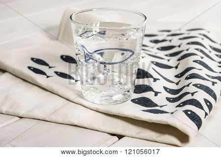 Water-filled Drinking Glass On Table Napkin With Blue Fish Design