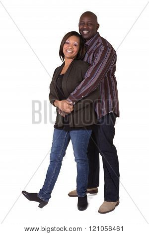 A middle aged couple standing close, isolated on white