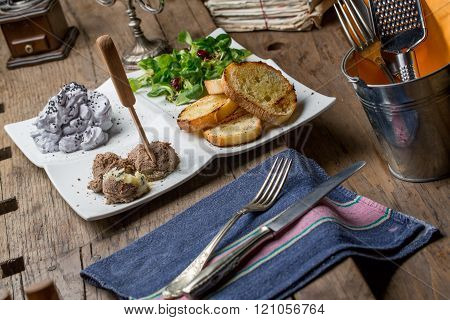 Tasty appetizers with chicken liver pate valerian salad toasted bread and blueberry mousse on an old wooden table