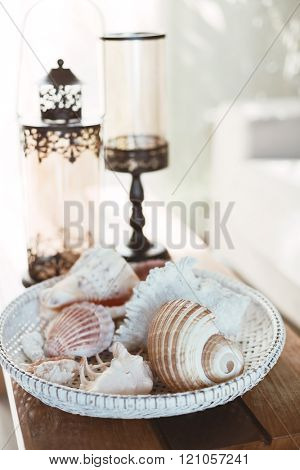 Beach interior decor: sea shells and lanterns on the wooden coffee table, natural colors. Detail of living room.