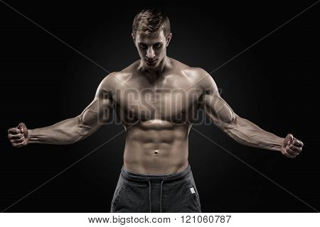 Stunning muscular man showing perfect abs, shoulders, biceps, triceps, chest