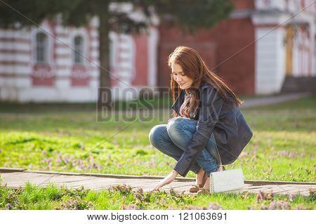 Brunette girl clothed in windbreaker hand touching young grass while walking on the  at springtime