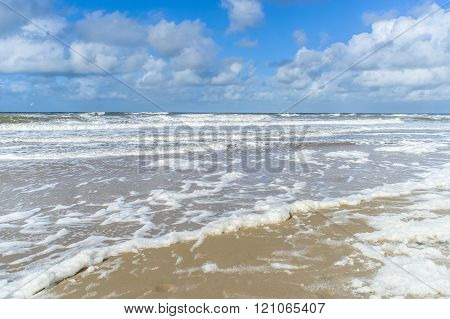 Wind And Waves Create Foam On The Beach