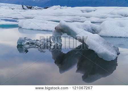 One angled ice shape being held by a transparent ice shape floating in Jokulsarlon glacial lagoon Iceland