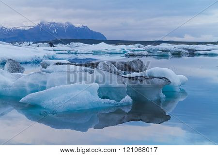 Luminous blue, white and black icebergs floating with mountains in the background, taken in Jokulsarlon glacial lagoon Iceland