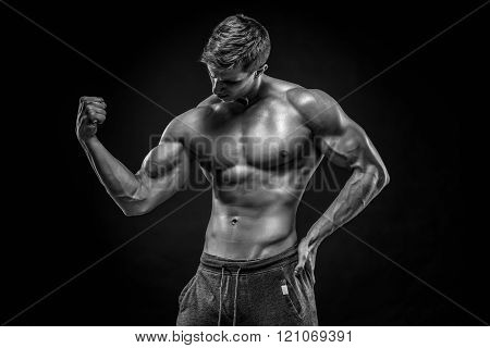 Stunning muscular man showing perfect abs, shoulders, biceps, tr