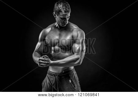 Stunning muscular man showing perfect shoulders, biceps, triceps