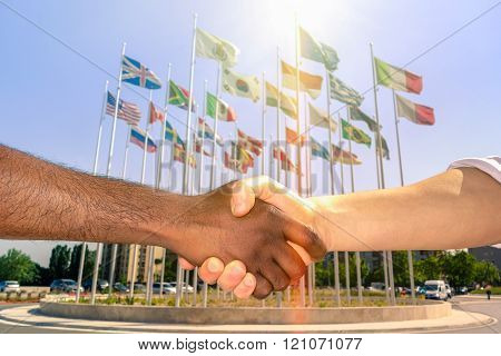 Multiracial Handshake With World Flags Background - Black And White Men Hand Shake Against Racism -