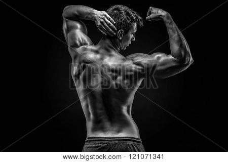 Healthy muscular young man showing back and biceps muscles