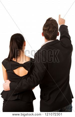 Confident business couple standing next to each other, pointing with finger to a bright future. Conceptual image.