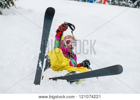 Kid in winter outfit lying in snow with skis