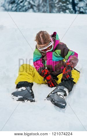 Kid in ski outfit buckling boots