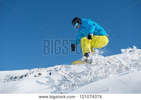 Snowboarder jumping over the snowy shrub while off-piste  riding