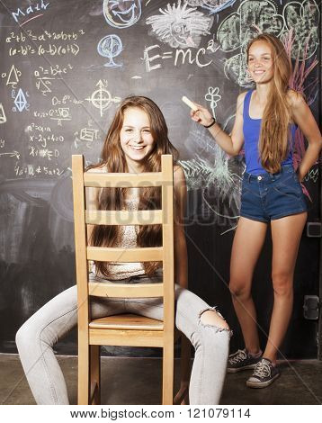 back to school after summer vacations, two teen real girls in classroom with blackboard painted toge