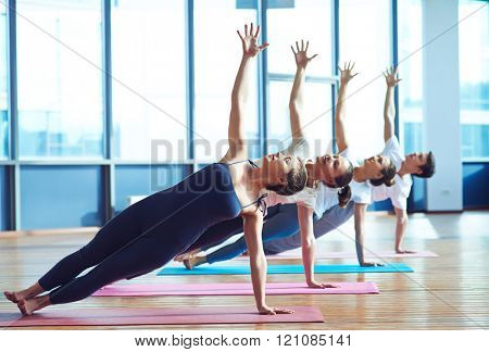Group of young people practicing side plank yoga pose during a class in gym