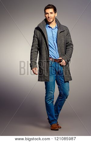 Full length portrait of a handsome man wearing jeans clothes and a coat. Men's beauty, seasonal fashion. Studio shot.