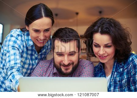 cheerful colleagues working with laptop in office